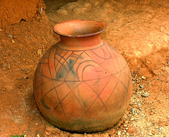 A vase sitting on top of a dirt field