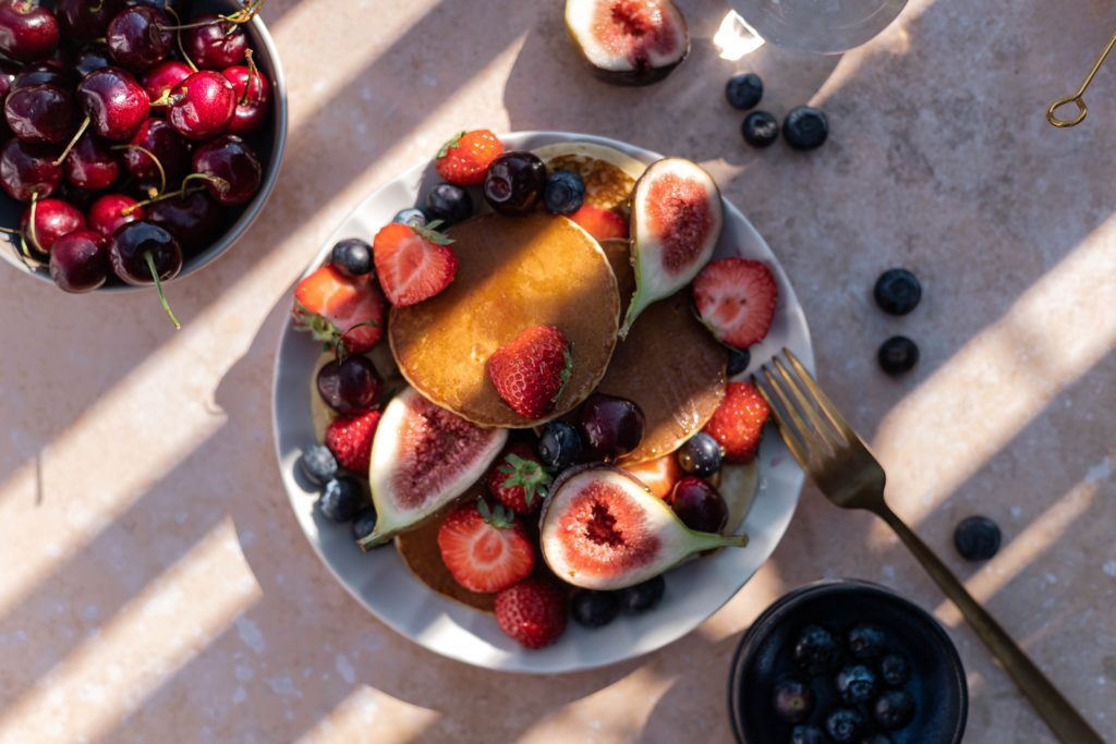 A cake with fruit on top of a wooden table